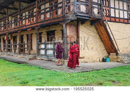 Bumthang Bhutan - September 13 2016: Three monks at the Kurjey Lhakhang (Temple of Imprints) in Bumthang valley Bhutan.