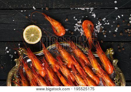 Set of shrimps closeup. Boiled shrimp with lemon on a wooden background.