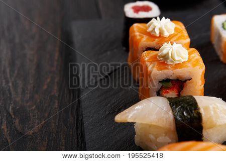 Sushi plate. Japanese food restaurant, unagi and salmon rolls closeup on dark background. Pov with copy space on black wood