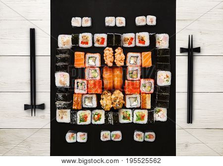 Japanese food restaurant delivery - sushi maki, unagi, gunkan and roll big party platter set on white wood background, above view
