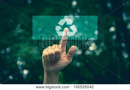Hand pressing button ecology interface with arrow recycling. Hand pressing recycling symbol on button touch screen. Environmental concept recycle.
