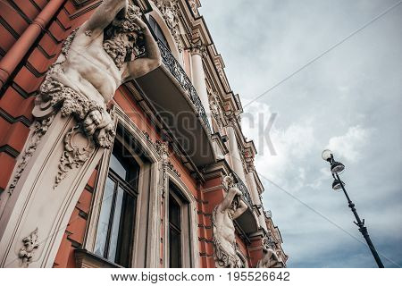 Facade of an ancient building in St. Petersburg with statues, toned