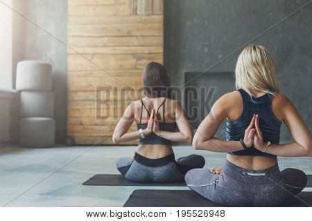 Women in yoga class making asana exercises. Girls do Reverse Prayer Pose, back and shoulders stretching. Healthy lifestyle in fitness club.