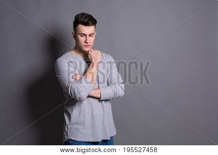 Pensive youn man studio portrait on grey background. Copy space, boy style, trendy hipster with cool hairstyle