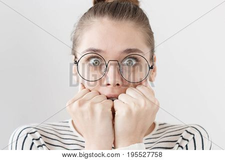 Indoor Closeup Of European Teenage Girl In Big Glasses Isolated On Grey Background With Round Big Ey