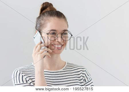 Side portrait of young European female isolated on gray background wearing hipster eyeglasses listening to interlocutor on smartphone showing satisfied happy smile from news she is hearing. poster