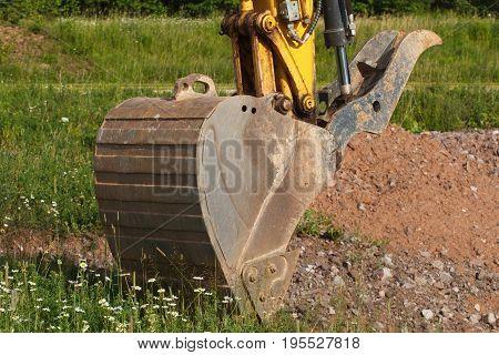 Excavator bucket detail in undeveloped outdoor area