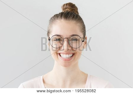 Indoor Portrait Of Young Beautiful Woman Isolated On Gray Background, Smiling, Blinking Behind Big R