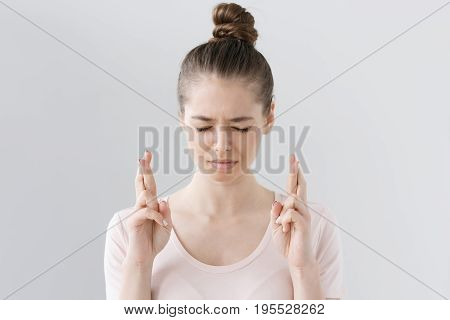 Indoor Photo Of Young Beautiful Female Isolated On Grey Background, Looking Deeply Concentrated With