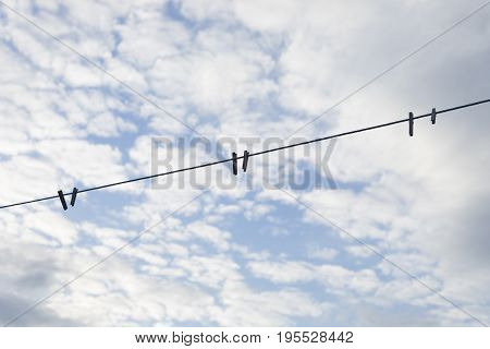 Clothespins clipped onto a clothesline in front of a blue and cloudy sky.