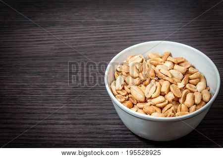 Peanuts. Bowl of salted peanuts on wooden table. Peanuts snack. Food concept.