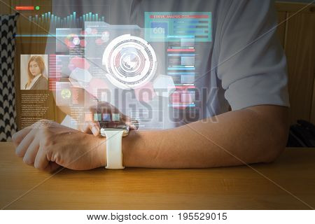 Male Hand using Digital Wireless Smart Watch with Virtual Reality Environment Hologram on Table as Modern Technology Lifestyle Concept.