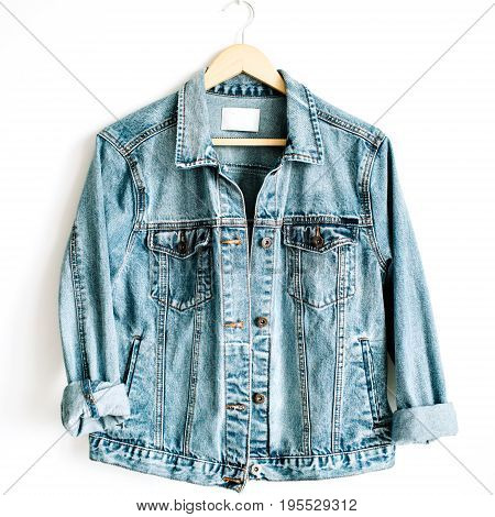 Beautiful trendy blue denim jeans jacket on hanger near white background. Fashion concept. Flat lay top view