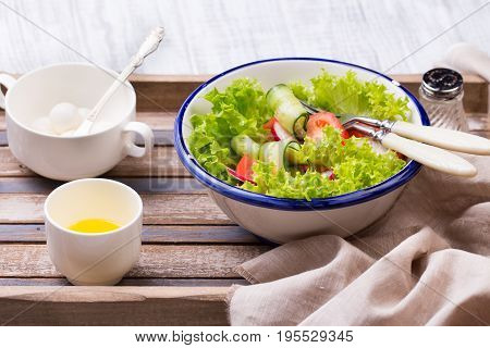Breakfast in bed. Fresh healthy salad. Tomato, letucce and traditional italian cheese Mozzarella in enamel bowl on wooden tray. Healthy food concept.