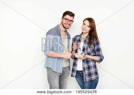 Couple in casual at white isolated background. Happy couple eating eating healthy food from take away box, man approving it with thumb up
