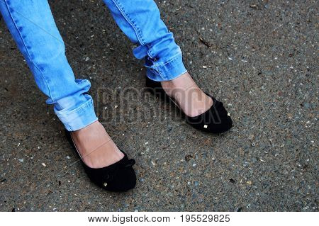 Women's Feet In Blue Jeans And Black Sneakers Close Up