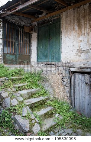Front entrance of an abandoned deserted house with closed doors and stairs.