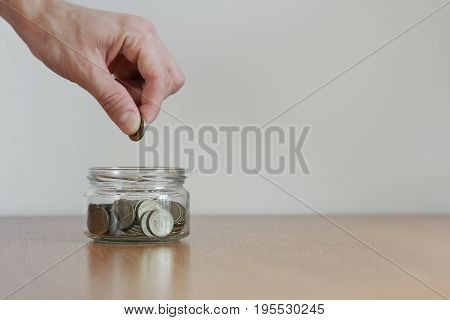 Hand Putting Money Coin In To The Glass Jar