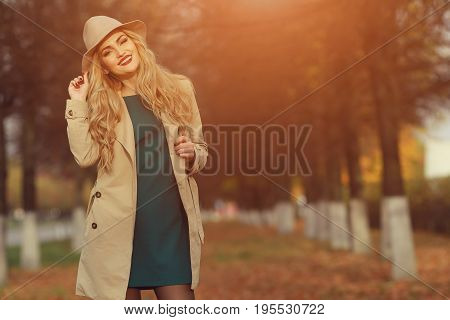 Young Beautiful Girl In A Beige Hat And Coat In A Park Autumn Park. Fashionable Female With Red Lips