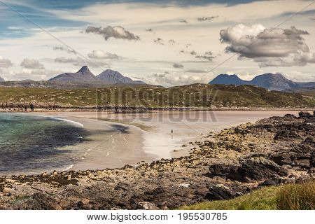 Assynt Peninsula Scotland - June 7 2012: Achnahaird Beach is sandy with gentle Atlantic Ocean waves out of Enard Bay. Lone walker far on beach. Mountainous background. Rocky foreground. Heavy clouds