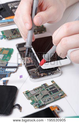 Repairing mobile phone, smartphone diagnostic at service center, repairman workplace