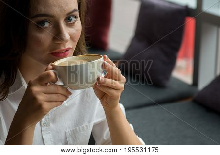 Pretty Girl With A Pimply Face Enjoys A Fragrant Coffee Sitting In Coffee House. Business Woman Rest