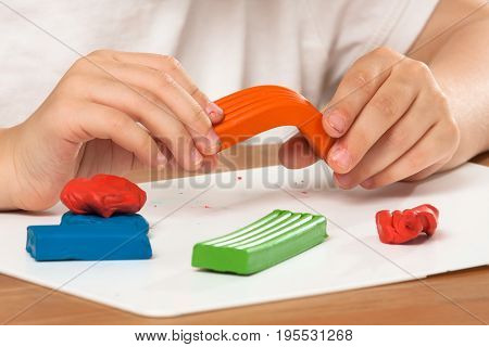hands of child molding from colourful clay plasticine on the table