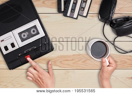 Revolution concept. Retro cassette tape recorder with headphones and cassettes lying on wooden table. View of woman`s hands pressing button on cassette player and holding cup of tasty coffee