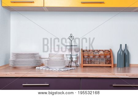 Composition with crockery and set of spices on counter in kitchen