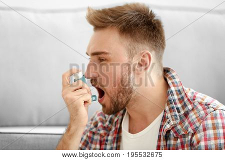 Young man using inhaler for asthma and respiratory diseases at home