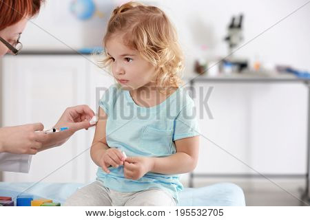 Doctor vaccinating child in clinic