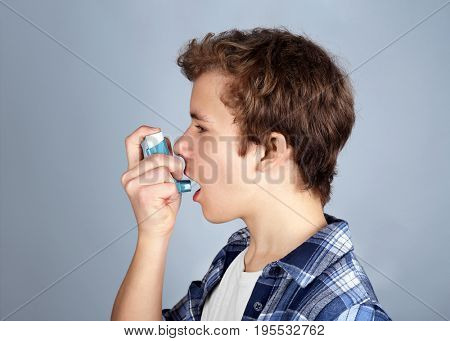Young boy using inhaler for asthma and respiratory diseases on light background