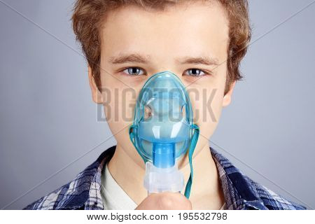 Young boy using nebulizer for asthma and respiratory diseases on light background