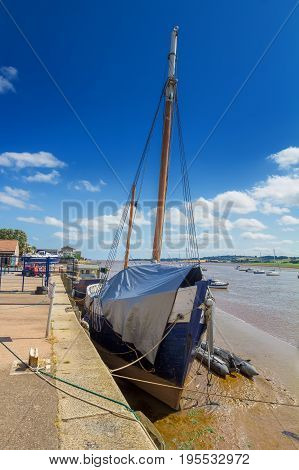 An old ship with a mast. Covered with tarpaulin. Moored at the shore at low tide. Topsham. Devon. England