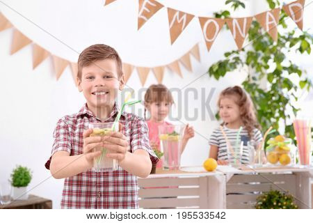 Cute little boy holding glass of lemonade and blurred stand with girls on background