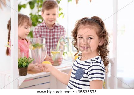 Cute little girl buying lemonade from kids at stand