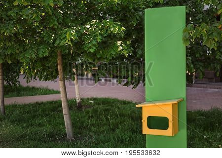 Container for storage of dog waste bags in park