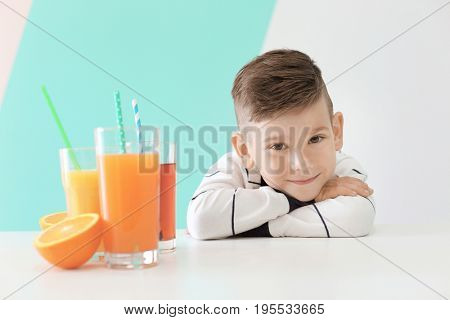 Cute little boy with glasses of juice sitting at table, on color background