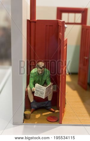 A serious man taking care of business on his phone in the bathroom