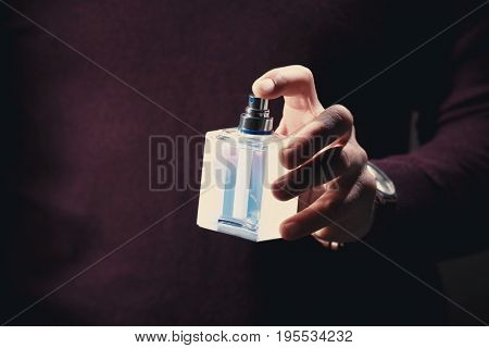 Young man with bottle of perfume, closeup