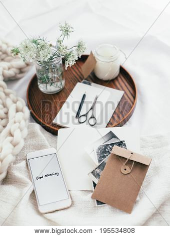 Wooden tray with smartphone, old photos, candle and spring flowers on white bedding. Relaxing and posting to blog in bed at home.
