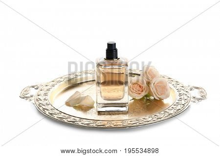 Metal tray with bottle of perfume and flowers on white background