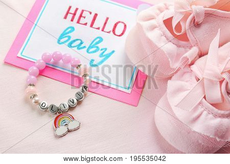 Bracelet with baby name OLIVIA, greeting card and booties on light cloth