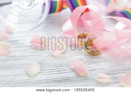 Beautiful composition with rings for lesbian wedding on wooden background