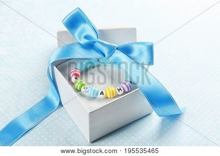 Bracelet with baby name NOAH in gift box on color cloth