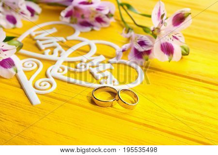 Beautiful composition with rings for lesbian wedding on color wooden background