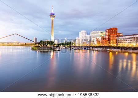 Night view on the Rhein river with illuminated buildings and television tower in Dusseldorf city, Germany