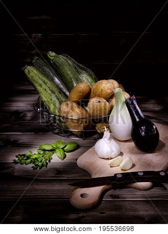 Potatoes zucchini onions garlic basil and parsley photographed on an antique wooden table with the technique light painting