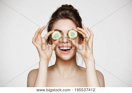 Young beautiful nude girl smiling hiding eyes behind cucumber slices over white background. Beauty skincare and cosmetology. Copy space.