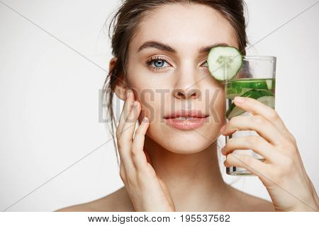 Close up photo of beautiful nude girl smiling looking at camera holding glass of water with cucumber slices over white background. Healthy nutrition. Beauty and skincare.